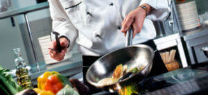 food service - chef cooking food in a steel wok